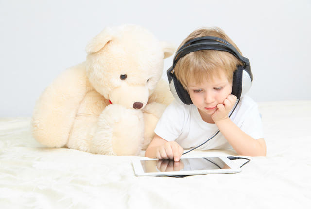 little boy with headset using touch pad